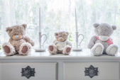 Many bear doll and candle on table and windowsill background — Stock Photo