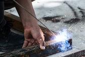 Woker welding steel with sparks lighting — Stock Photo