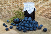 Still life with blueberries, confection, jam and twigs — Stock Photo