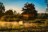 Small boat anchored near the cottage during the sunrise — Stock Photo