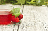Cup of tea with strawberries on wooden table — Stock Photo