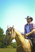 Young cowboy man ridig with horse — Stock Photo