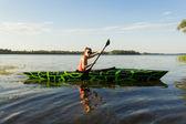 Girl with paddle and kayak — Stock Photo