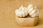 Garlic in a wooden bowl on sack background. — Stock Photo