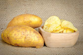 Potato chips in a wooden bowl and fresh potatoes — Stock Photo