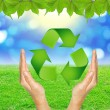 RECYCLE sign in hands against green spring background. — Stockfoto #51320303