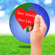 Red paper shape in hand and globe on grass background. environme — Stock Photo #51320469