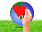 Blank red paper shape in hand and globe on grass background. — Stock Photo