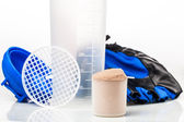 Scoop of whey protein in front of gym equipment: gloves and shak — Stock Photo