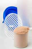 Scoop of chocolate whey isolate protein in front of protein shak — ストック写真