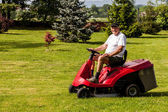 Senior man driving a red lawn mower — Stock Photo