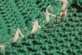White knots in a green fishing net — Stock Photo