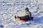 A boy sledding down the hill — Stock Photo