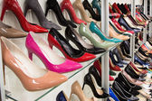Rows of beautiful women's shoes on store shelves — Stock Photo