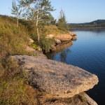 costa di lago con pietre e rocce. calma acqua blu del lago — Foto Stock #44063349