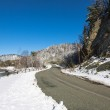 Winter snowy road on the background of mountains and blue sky. — Stock Photo #46062873