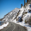 Winter snowy road on the background of mountains and blue sky. — Stock Photo