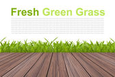 Fresh spring green grass on white and wood floor background — Stock Photo