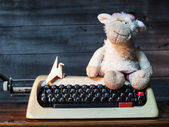 Typewriter with paper bird and Dolly the sheep — Stockfoto