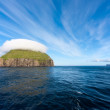Uninhabited island with bizarre cap of clouds — Foto Stock #38757279