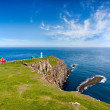 Stock Photo: Lighthouse on rocky promontory