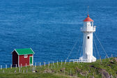 White lighthouse and red cabin on a sea cliff — Stock Photo