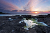Sunset over a tidal pool . Rocky coast of Scotland . — Stock Photo