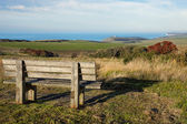 Empty wooden bench facing english countryside — Stock Photo