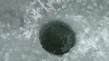 Ice-hole for fishing on the ice of the river in winter — Stockvideo