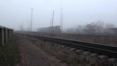 Train runs on rails in fog autumn — Stock Video