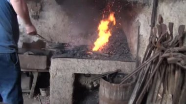 Blacksmith is hammering red-hot piece of iron — Stock Video