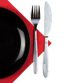 Plate, fork and knife on a napkin — Stock Photo