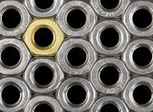 Golden screw nut in steel nuts — Stock Photo