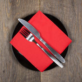 Fork, knife and red napkin on black plate — Stock Photo