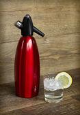 Röd soda siphon och soda glas med is — Stockfoto