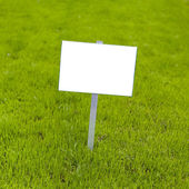 Sign on grass whith isolated space for caption — Stock Photo