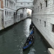 Stock Video: Gondolsails through narrow canal in Venice