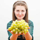 Beautiful girl offers grapes — Stock Photo