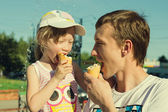 Father and daughter eating ice cream while walking — Stockfoto