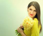 Vacker flicka med en bukett blommor — Stockfoto