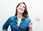 Attractive cheerful woman with candy in the form of heart — Stock Photo