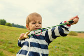 A boy learns to shoot a slingshot — Stock Photo