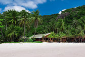 Paradise beach with bungalows and mountains — Stock Photo