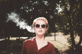 Smoking young woman with glasses in the yard — Stock Photo