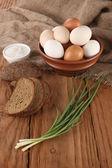Raw eggs in an earthenware bowl, onions, bread, salt shaker  — Stockfoto
