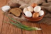 Oeufs crus dans un bol en terre cuite, oignons, pain, salière — Photo