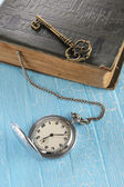 Vintage pocket watch, old book and a brass key — Stock Photo