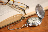 Vintage pocket watch glasses  and open old book  — Stock Photo