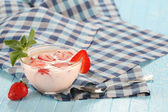 Strawberry with yogurt in a glass bowl on a wooden board  — Stockfoto