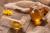 Honey in a glass bowl on a wooden boards background — 图库照片